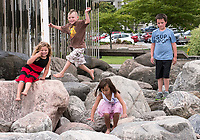 What would summer be without exploring MacPherson Fountain in Centennial Park? Jason Beauvais, 6, brown shirt, and sister Kayln, 4, red dress and Cordell Shipman, 8, blue shirt and his sister Jennaka, 5, spent time exploring the rocks and Fountain with grandmother Debra Beauvais and Theresa Shipman, recently.
