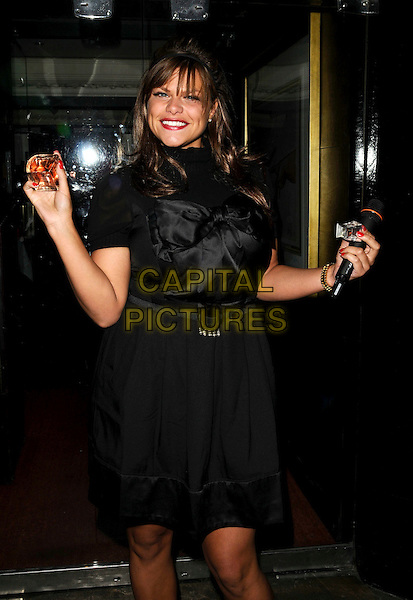 "JADE GOODY.Perfume launch of her new fragrance ""Controversial"", Embassy Club, London, England..July 29th, 2008.half 3/4 length black dress silk satin bow ribbon bottle microphone.CAP/CAN.©Can Nguyen/Capital Pictures."