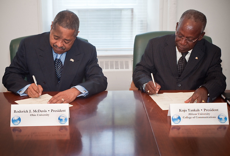 President McDavis and African University President Kojo Yankah sign international agreement.