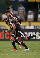 WASHINGTON, DC. - AUGUST 22, 2012:  Andy Najar (14) and Marcelo Saragosa (11) of DC United congratulate Brandon McDonald (4) for his goal against the Chicago Fire during an MLS match at RFK Stadium, in Washington DC,  on August 22. United won 4-2.