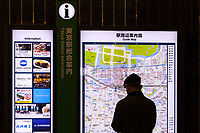 An older man in silhouette checks a information panel inside Tokyo Station, Marunouchi, Tokyo, Japan. Friday, January 10th 2014
