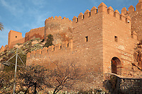 The Torre de la Guardia watchtower and entrance gate to the Alcazaba, a 10th century fortified enclosure and royal residence in Almeria, Andalusia, Southern Spain, with crenellated ramparts above. The Alcazaba was begun in 955 by Rahman III and completed by Hayran, Taifa king of Almeria, in the 11th century. It was later added to by the Catholic monarchs. Picture by Manuel Cohen