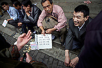 Rural workers gather at a labour market in the southwestern Chinese megapolis of Chongqing in search of jobs as chefs. They are holding placards stating the dishes they can cook. The cooks say when they can get a job they earn 2,000 - 7,000 yuan per month, a phenomenal improvement over tilling the fields. The Chinese government plans to move 250 million rural residents into urban areas over the coming dozen years though it is unclear whether people want to move and where the money for this project will come from. Further urbanisation is meant to drive up consumption to counterbalance an export orientated economy and end subsistence farming but the drive to get people off the land is causing tens of thousands of protests each year. /Felix Features