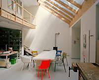 The open plan studio has a dining area furnished with a long white dining table and a collection of Stefan Diez's chairs positioned underneath a vast skylight