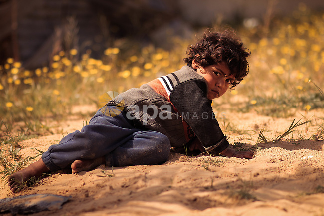 A boy lies on the sand with hard look. Photo by Sanad Ltefa