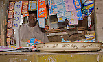 A street vendor in Lagos, Nigeria peers out from inside his market stall.