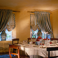 Striped blue and white curtains with festoon blinds dress the windows in this stencilled dining room