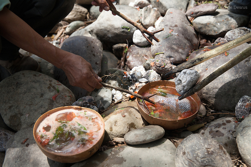 Don Victor Santiago Olivares places a hot stone in the caldo de piedra on the banks of the Usila River in San Felipe Usila, Mexico on March 30, 2016. Caldo de piedra, or stone soup, is an ancestral dish of the indigenous Chinantec people of San Felipe Usila, a remote village in northern Oaxaca state, Mexico. Traditionally prepared by men in a ritual that dates back to pre-Hispanic times, the soup is cooked in jícara (gourds) by glowing-hot white river rocks that have been heated on a bonfire of orangewood. Ingredients include whole mojarra fish, tomatoes, onion, garlic, chile, epazote, cilantro and fresh water; the soup is seasoned with lime and salt and eaten on the banks of the Usila river. Photo by Bénédicte Desrus