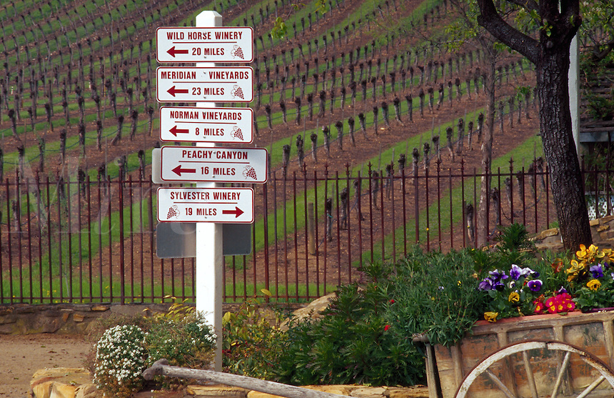 Quaint view of winery distance signs outside of a vineyard. Paso Robles, California.
