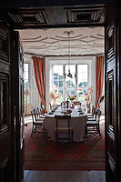 A view through an open door into the dining room, with its coffered ceiling and floor-to-ceiling windows