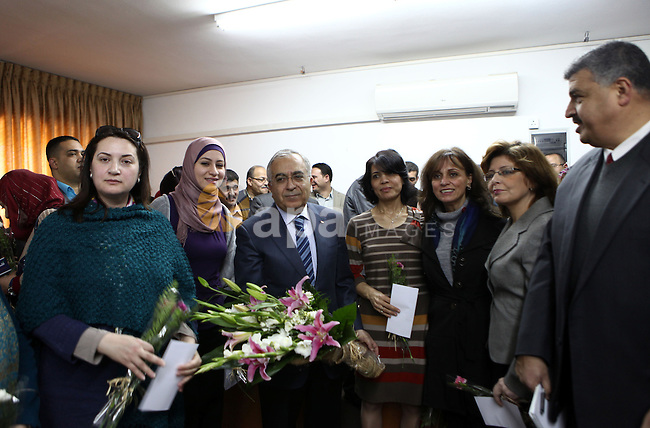 Palestinian Prime Minister, Salam Fayyad, honors women work in the Ministry of Housing and Public Works during a celebration organized on the occasion of Women's Day in the West Bank city of Ramallah, on Mar. 07, 2012. Photo by Mustafa Abu Dayeh.