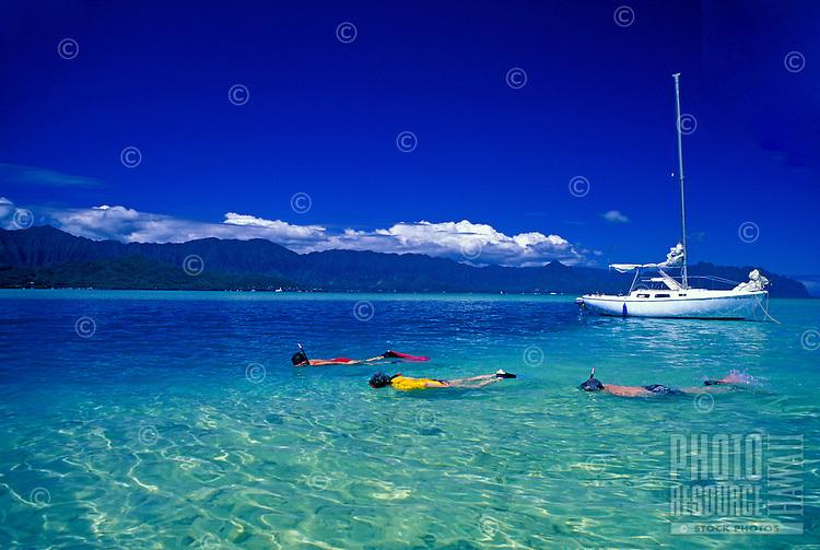 Snorkelers near sailboat in the crystal clear waters near Ahu O Laka sandbar, Kaneohe Bay, Oahu
