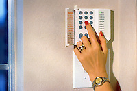 Woman's hand touching keypad for home security system.