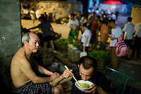 "A man eats fried noodles and xifan, rice porridge or congee, small unnamed outdoor noodle cafe at the bottom of Shibati, or 18 Steps, in central Chongqing. The cook, Tong Su Chun, has been cooking at the spot, which is run by his nephew, for about 20 years. The neighborhood is slated for redevelopment, and all residents, including this shop, must leave the area by October 2014. Tong Su Chun said he didn't know what he would do after the restaurant closes. ""I'll take a break,"" he said, ""and then find something new."" The restaurant typically serves a couple hundred people in a night, most spending about 15 RMB."