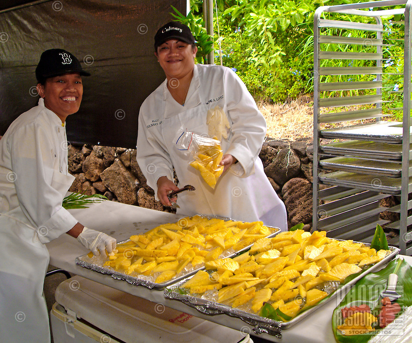 Two workers serve up the fresh pineapple at the Academy of the Pacific's annual luau fundraiser.