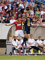 Fabio (20) of Manchester United goes up for a header against Sebastien Le Toux (9) of Philadelphia Union during a friendly match at Lincoln Financial Field in Philadelphia, Pennsylvania.  Manchester United defeated Philadelphia Union, 1-0.