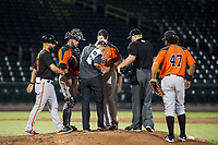 AZL Giants athletic trainer Charlene Wichman looks at the finger of relief pitcher Sidney Duprey (61) as manager Hector Borg, catcher Jeffry Parra (5), home plate umpire Ray Patchen, and first baseman Nathanael Javier (47) look on against the AZL Cubs on September 6, 2017 at Sloan Park in Mesa, Arizona. AZL Giants defeated the AZL Cubs 6-5 to even up the Arizona League Championship Series at one game a piece. (Zachary Lucy/Four Seam Images)