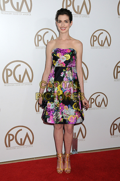 Anne Hathaway.At the 24th Annual Producers Guild Awards held at the Beverly Hilton Hotel, Beverly Hills, California, USA, .26th January 2013..PGAs PGA arrivals full length dress  navy blue clutch bag gold strappy sandals  open toe t-bar strapless floral print smiling  purple pink green yellow black .CAP/ADM/BP.©Byron Purvis/AdMedia/Capital Pictures.