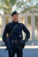 A security guard in the ruler's special protection force, with earpiece connected to a two-way radio, holding a machine gun.  He is wearing a bullet-proof vest as body armour.