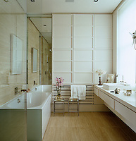 A wall of lacquered cupboards provides storage in this elegant bathroom