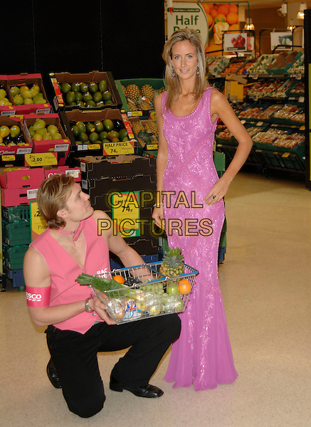 LADY VICTORIA HERVEY.At a photocall for Tesco, as they launch a free personal butler servicein the UK, West Cromwell Road, .London, England, February 27th 2007..full length long pink sparkly dress hand on hip butler bending kneeling basket of food shopping funny.CAP/PL.©Phil Loftus/Capital Pictures