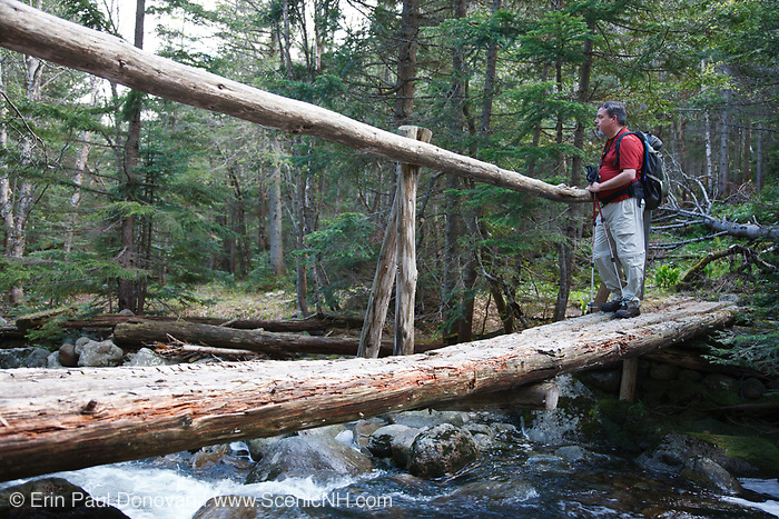 A hiker enjoys the brook from a foot bridge on the Asquam Ridge Trail during the summer months in the White Mountains, New Hampshire USA.