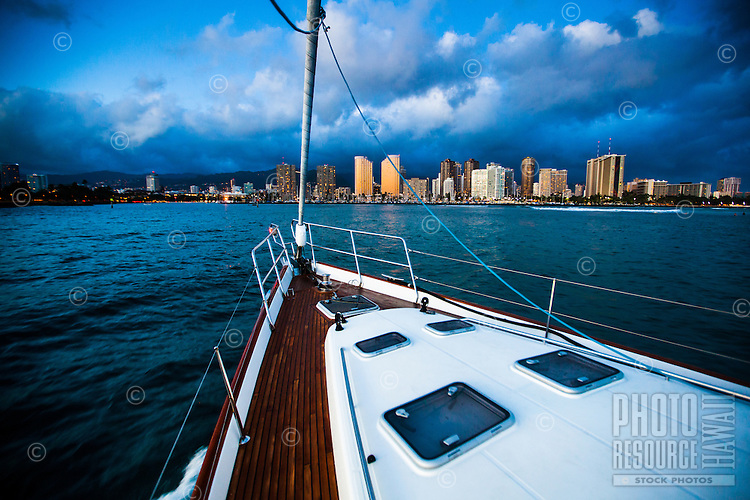 A yacht sails back into Ala Wai Harbor at sunset, with Magic Island on the left and Waikiki hotels on the right, O'ahu.