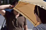 July 11, 2011 - Tokyo, Japan - A woman is seen holding a fashionable parasol in downtown Tokyo. Japanese people, especially middle-aged women, use parasols during the hot Summer months to avoid any form of skin cancer. Today, parasols are also becoming popular among young adult women due to various designs and colors available on the market. (Photo by Yumeto Yamazaki/AFLO)