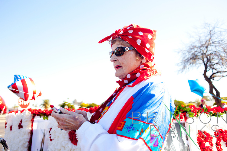 A woman in the Rose the Riveter Club applies lipstick as she waits for her turn to join the parade in the Bell Recreation Center lot before the Sun City Parade in Sun City, Arizona March 13, 2010. 2010 marks the 50th anniversary of Sun City, the first planned retirement city in the United States.
