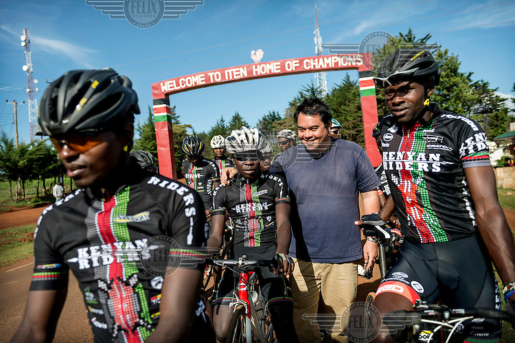 The Kenyan Riders, a Kenyan cycling team, gather before an arch over the road at the entrance of Iten which bears a slogan welcoming visitors to the 'home of champions'. The team have been training along the road between Eldoret and Iten, a small town in the highlands on the edge of the Great Rift Valley at an altitude of 2400 metres, a perfect location for high altitude training. The team is managed by Singaporean Nicholas Leong (pictured) and trained by Australian Simon Blake.