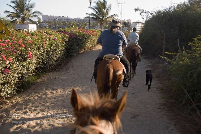 Tourists and guide horseback riding in Cabo San Lucas, Baja California, Mexico
