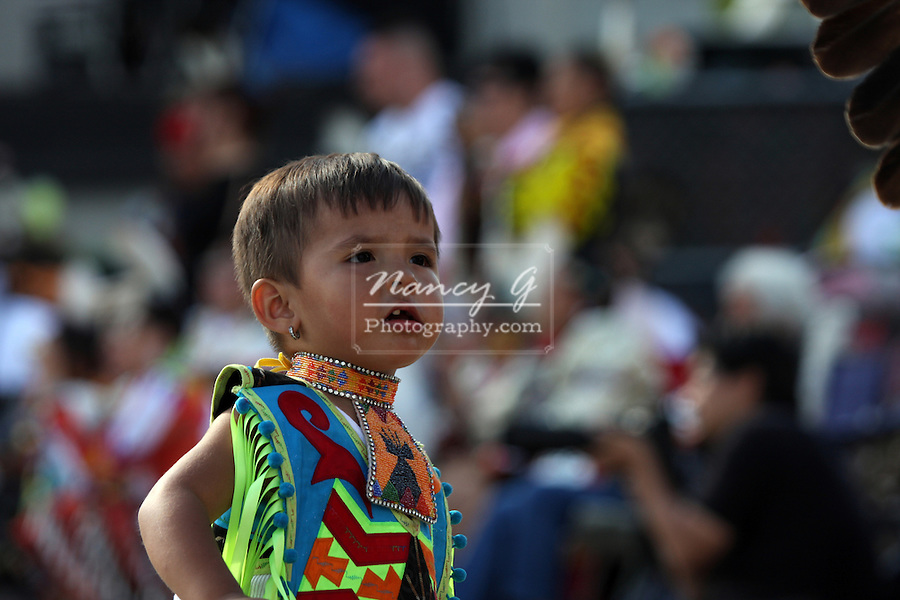 A young Native American Indian boy watching others dancing at a Pow Wow at the Milwaukee Lakefront Indian Summer Festival, Wisconsin
