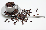Coffee beans cup spoon saucer on white background