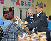 Washington, D.C. - November 25, 2009 -- United States President Barack Obama, accompanied by his wife Michelle and daughters Sasha and Malia hand out food to the homeless at Martha's Table in Washington, D.C. on Wednesday, November 25, 2009..Credit: Ron Sachs / Pool via CNP