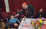 Cardinal Timothy Dolan, the archbishop of New York and chair of the Catholic Near East Welfare Association, gives a bite of cake to Henry Samir, a 6-year old child with disabilities, in the Mar Narsai Clinic in Dahuk, Iraq, on April 10, 2016. The clinic was built and equipped by CNEWA to meet the needs of Christians and others displaced to Dahuk because of attacks by ISIS.<br /> <br /> Cardinal Dolan came to Iraqi Kurdistan with Bishop William Murphy of Rockville Centre and other church leaders to visit with Christians and others affected by ISIS. <br /> <br /> CNEWA is a papal agency providing humanitarian and pastoral support to the church and people in the region.