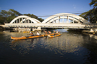 Outrigger canoe paddling under the Anahulu Bridge, Haleiwa, North Shore of Oahu