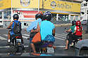 Motorcyclists stopping at traffic lights in the morning. Cuiaba, Mato Grosso, Brazil