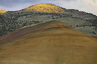 Medium shot of a Painted Hill below a sunlit mountain peak. Painted Hills, John Day Fossil Beds National Monument, Oregon.