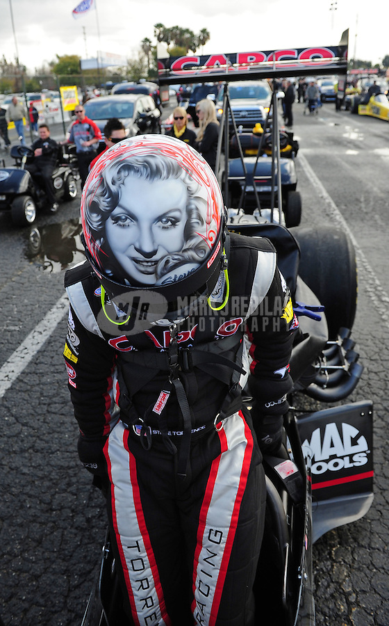 Feb. 12, 2012; Pomona, CA, USA; NHRA top fuel dragster driver Steve Torrence climbs into his car wearing a helmet with the likeness of Marilyn Monroe painted on it during the Winternationals at Auto Club Raceway at Pomona. Mandatory Credit: Mark J. Rebilas-