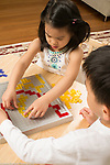 4 year old girl and 6 year old brother playing strategy game Blokus