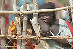 Displaced women watch through a fence as food is distributed on April 7, 2017, to hungry people in Rumading, a village in South Sudan's Lol State where more than 5,000 people, chased from their homes by drought and conflict, remain in limbo. In early 2017, they set out walking for Sudan, seeking better conditions, but were stopped from crossing the border. They remain camped out under the trees at Rumading, eating wild leaves as the rainy season approaches. <br /> <br /> In early April, Norwegian Church Aid, a member of the ACT Alliance, began drilling a well in the informal settlement and distributed sorghum, beans and cooking oil to the most vulnerable families. The ACT Alliance is carrying out the emergency assistance in coordination with government officials and the local Catholic parish.
