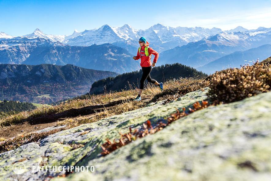 A female trail running on the Gemmenalphorn, in autumn, above Interlaken, Switzerland with the Eiger, Mönch and Jungfrau in the distance.