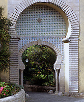 A Moorish style arch that features patterned tiles leads to the gardens of the palace