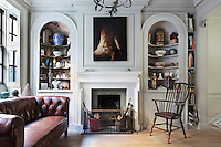 The living room fireplace is flanked by two alcoves with shelves weighed down with objects and collectibles