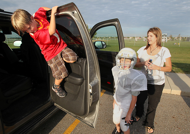 Keenan Jacobs, 7, climbs on a door while his mother, Heather, works to load up the family SUV with Justin, 10, for busy evenings of activities.  Heather lost her husband, Eric, in a plane crash in 2006 when she was eight months pregnant with their youngest, Ella, and has since been raising her five young children on her own.
