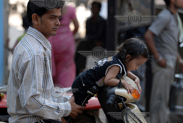 Man and his daughter on a motorcycle in central Mumbai.