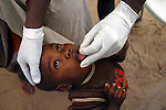 Health worker giving child an oral vaccine, Chad