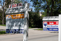 """For sale"" signs for Re/Max and Zappia Group realty are seen next to each other in Winnipeg Thursday May 26, 2011."