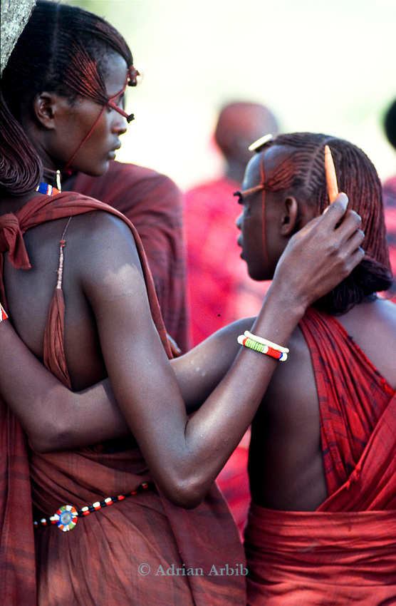 Maasai moran spend hours on their appearance.  Shortly their heads will be shaved by their mothers as part of the initiation into manhood.<br /> Kajiado, Kenya.