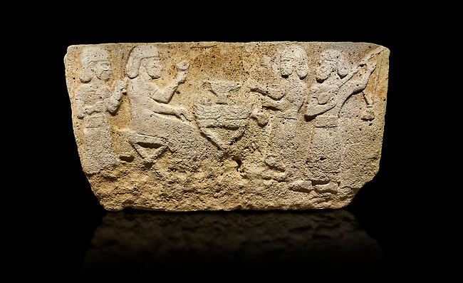 Hittite monumental relief sculpted orthostat stone panel from Water Gate Limestone, Karkamıs, (Kargamıs), Carchemish (Karkemish), 900-700 BC.  Anatolian Civilisations Museum, Ankara, Turkey.<br /> <br /> The figure sitting on a stool to the left of the table holds a goblet in his right hand which he raised upwards. Behind, there is a servant with a fan in his hand. On the other side of the table is another servant waits with a vessel in the hands. The rightmost figure plays a Saz (a stringed musical instrument) with the tassel on the handle. <br /> <br /> On a black background.